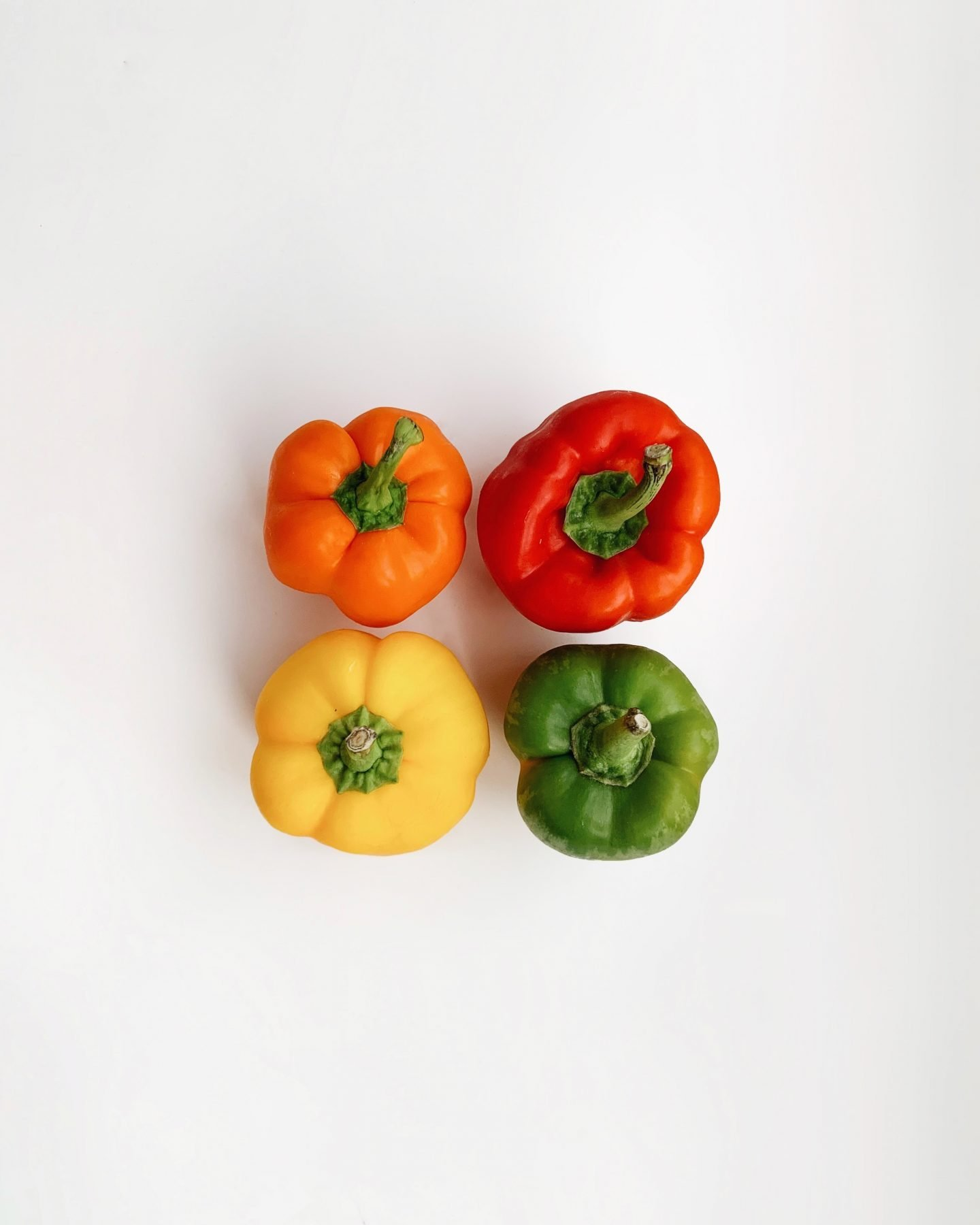 4 capsicums on white surface